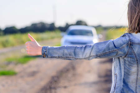 flagging: Young woman hitchhiking in the countryside flagging doan an approaching car on a farm road with her thumb