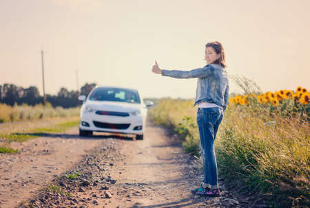 telecommute: Woman in denim jacket and jeans standing hitchhiking on a rural dirt road flagging down an approaching car, view from the rear