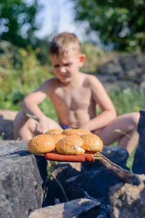 niño sin camisa: Sentado Sin camisa muchacho joven que asa a Pan y Salchichas en los palillos para el almuerzo en un día muy soleado día. Foto de archivo