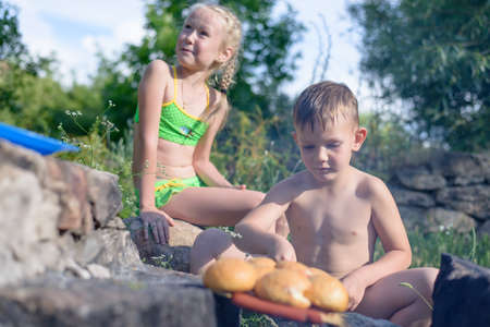 hot guy: Two cute children, boy and girl, getting tanned at a barbecue with sausages and buns, outdoors, in a sunny day of summer