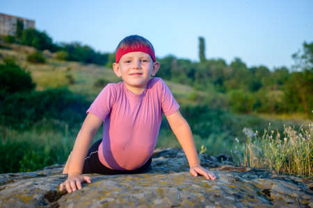 wry: Cute little boy trying to do press-ups as he works out on a rock looking up at the camera with a wry smile, fitness and active lifestyle concept