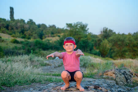 supple: Supple young boy practicing pilates outdoors standing barefoot balancing on one leg on a rock in the countryside with a look of concentration in a health and fitness concept, with copyspace