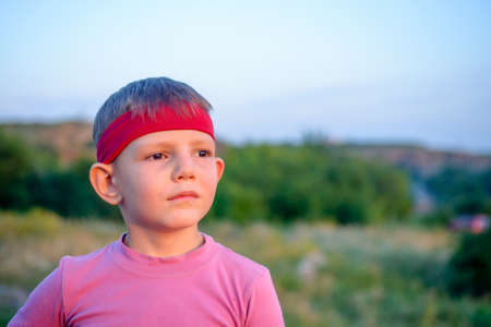perturbed: Close up of the face of a handsome young boy wearing a red headband staring into the distance into the setting sun with a dreamy expression
