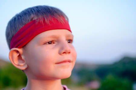preteen boys: Close up of the face of a handsome young boy wearing a red headband staring into the distance into the setting sun with a dreamy expression