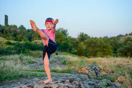boy barefoot: Supple young boy practicing pilates outdoors standing barefoot balancing on one leg on a rock in the countryside with a look of concentration in a health and fitness concept, with copyspace