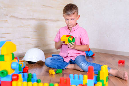 Cute cheeky young boy playing at home with colorful plastic building blocks holding up a toy to the camera with a grin Stock Photo