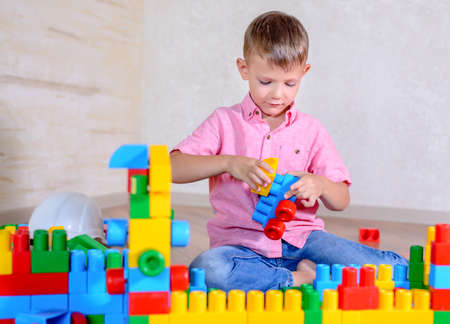 preteen boys: Young boy playing with colorful building blocks creating a robot and train engine turning to smile at the camera