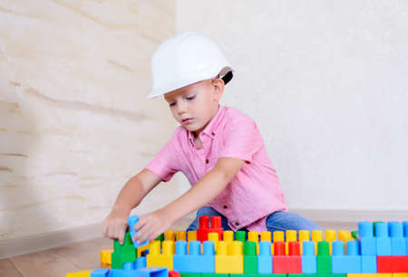 Young boy playing with colorful plastic interlocking building blocks wearing a hardhat as he pretends to be a builder or architect Stock Photo