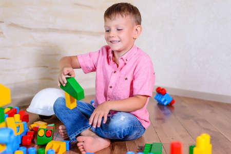 Happy young boy playing with his building blocks holding a finished creation in his hands as he grins cheekily at the camera Stock Photo