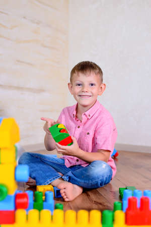 grins: Happy young boy playing with his building blocks holding a finished creation in his hands as he grins cheekily at the camera Stock Photo