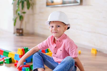 boy sitting: Happy little boy sitting on the floor and wearing plastic white hard hat, blue jeans and pink shirt while playing with toy construction blocks, at home