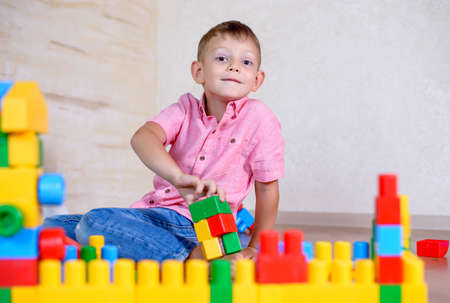 preteen boys: Cute cheeky young boy playing at home with colorful plastic building blocks holding up a toy to the camera with a grin Stock Photo