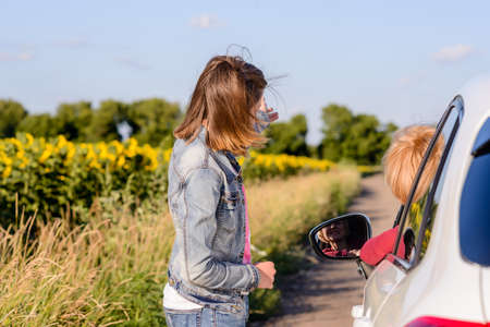 Friendly teenage girl wearing blue denim jacket and jeans while talking with a female driver stopped on a road in the countryside, in a sunny day of summer Standard-Bild
