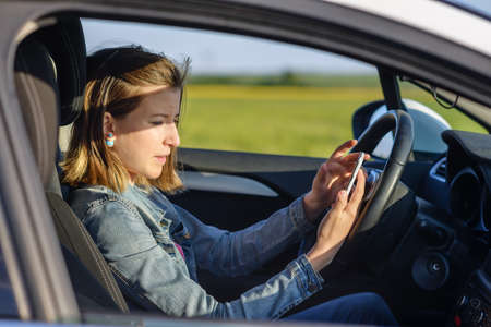 Dangerous female driver reading a text message on her smartphone and taking her attention off the road, profile view