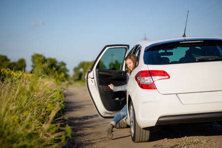 hitch hiker: Young woman climbing into the rear passenger seat of a car stopped on a country road looking back to smile at the camera Stock Photo