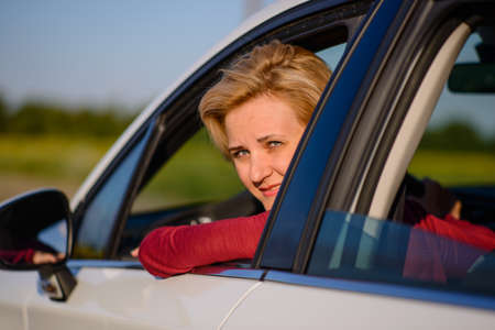poking: Smiling middle-aged female driver poking her head out of the open side window and turning to smile at the camera