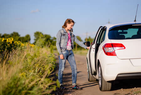 hitch hiker: Young woman opening a car door at the side of a country road as she prepares to enter the back seat