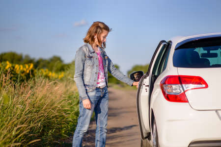 stopped: Young woman opening a car door at the side of a country road as she prepares to enter the back seat