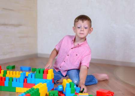 train engine: Young boy playing with colorful building blocks creating a robot and train engine turning to smile at the camera