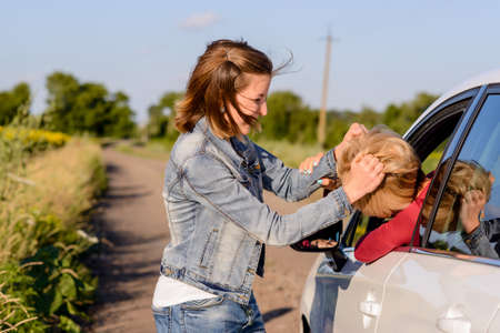 women fighting: Two women fighting at the roadside on a rural road with one inside and one outside the car fighting through the open drivers window