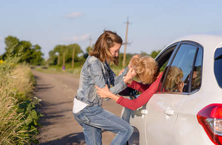 Two women fighting at the roadside on a rural road with one inside and one outside the car fighting through the open drivers window
