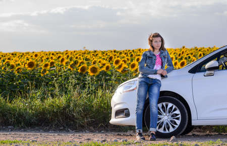 stopped: Young woman enjoying a day in the country standing leaning against her car in front of a field of colorful yellow sunflowers Stock Photo