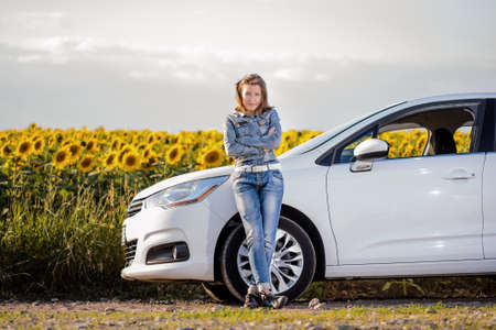 landowner: Young woman enjoying a day in the country standing leaning against her car in front of a field of colorful yellow sunflowers Stock Photo