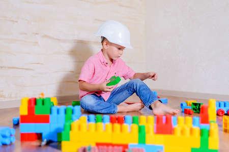 Creatieve jonge jongen spelen met een verzameling van veelkleurige bouwstenen die een bouwvakker draagt als hij zich voordoet als een architect of ingenieur