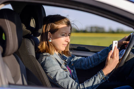 Young female driver reading a text message on her mobile phone as she drives along a rural road, distracting her attention from the road