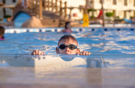 Young boy wearing sunglasses of goggles peering out of a swimming pool at the camera as he supports himself on the paving surround with his hands on a hot summer day Stock Photo