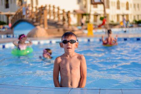 48474513 - Chico con gafas de sol o gafas de jóvenes sentados en el lado de  una piscina en el sol de verano con los pies colgando en el agua mientras  ... e864121fc690