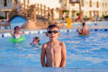 dangling: Young boy wearing sunglasses or goggles sitting at the side of a swimming pool in the summer sunshine with his feet dangling in the water as he smiles at the camera