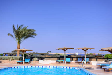 beachfront: Swimming pool and umbrellas at a luxury beachfront tropical resort for relaxation on a perfect summer vacation