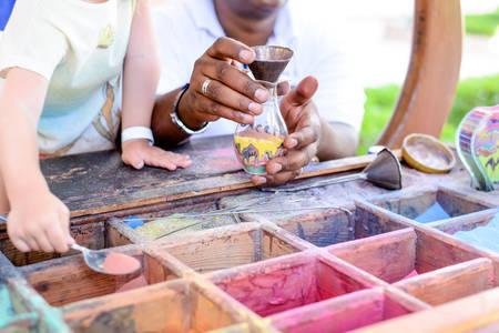 Jongen creëren van kleurrijke zand kunst vullen van een doorzichtige container met geassorteerde gekleurde pigmenten in een outdoor display