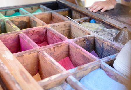 autochthonous: Colored powdered pigment or sand for making artwork in transparent containers displayed in a wooden box