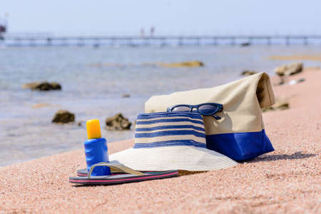 thongs: Ladies beach gear on a tropical beach with a sunhat, thongs, sunscreen and bag lying on golden sand overlooking the sea
