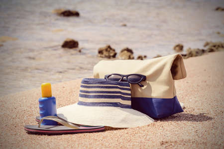 sunhat: Ladies beach gear on a tropical beach with a sunhat, thongs, sunscreen and bag lying on golden sand overlooking the sea