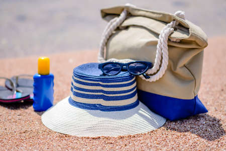sunhat: Beach gear on the sand overlooking the sea with a sunhat, sunscreen, slip slops and beach bag conceptual of a summer vacation in the tropics