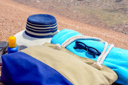 skin diving: Beach gear arranged neatly at the waters edge on a sandy tropical beach with a sunhat, bag, slip slops, towel, sunglasses and suntan lotion conceptual of a summer vacation