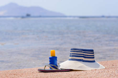 thongs: Sunhat, thongs and sunscreen lying on the golden sand on a beach overlooking a sheltered bay and ocean conceptual of a summer vacation at the seaside