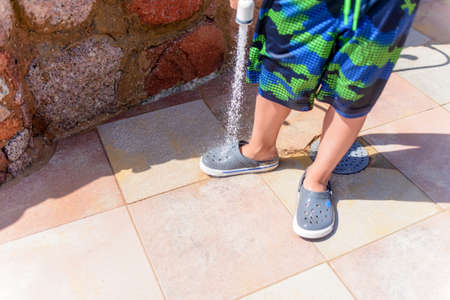 hosepipe: Young boy hosing the beach sand off himself and his shoe using a hosepipe at a tropical resort after coming in off the beach on his summer vacation