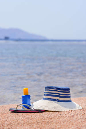 sheltered: Sunhat, thongs and sunscreen lying on the golden sand on a beach overlooking a sheltered bay and ocean conceptual of a summer vacation at the seaside
