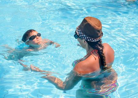 nadando: Chico joven que llevaba gafas de aprendizaje a nadar con su madre en una piscina, vista desde detr�s de la mujer de su rostro y la expresi�n decidida
