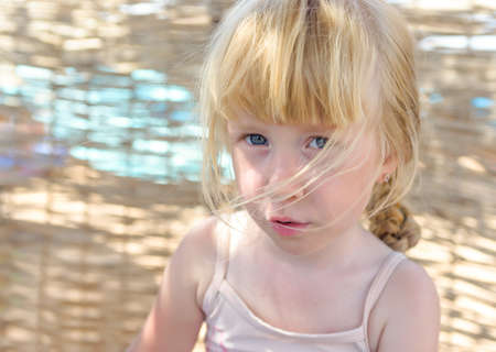 facial expression: Pretty little blond girl with a sulky expression looking up at the camera as she plays on her beach in dappled sunlight Stock Photo