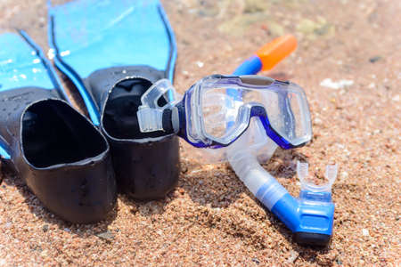 skin diving: Skin diving gear with a pair of flippers, goggles and snorkel lying on the sand at the edge of the ocean on a tropical beach