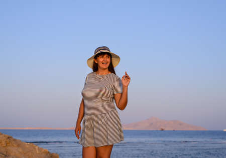 Trendy woman posing in evening light on a seashore overlooking a quiet ocean as she holds onto her hat in the summer breeze Stock Photo
