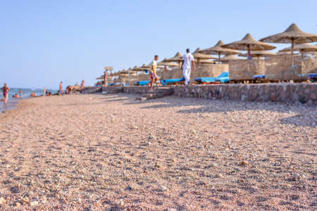 respite: Tourist beach at a tropical resort with thatched beach umbrellas and comfortable recliner chairs to relax in the sun, low angle view across the sand with some people visible