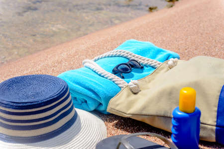 thongs: Assorted beach accessories on the sand of a tropical beach overlooking the water with a sunhat, sunscreen, towel, thongs, sunglasses and beach bag