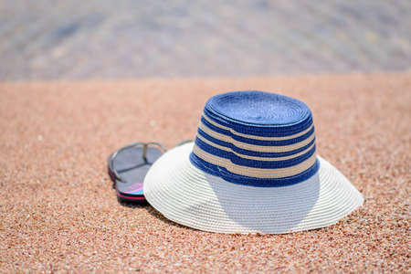 thongs: Trendy sunhat and beach thongs or slip slops lying on the golden sand of a tropical beach in the summer sun conceptual of a tropical vacation or getaway