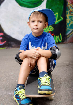 elbow pads: Portrait of Serious Young Boy Wearing Elbow Pads and Baseball Cap Sitting on Skateboard in Urban Setting with Graffiti Covered Wall in Background